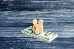 La gente e un bambino stanno stando su un mucchio dei dollari Supporto della gente sui soldi Pagando le tasse, riceventi i benefi Immagine Stock