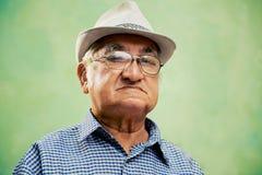 Ritratto dell'uomo anziano serio con il cappello che esamina macchina fotografica Immagine Stock
