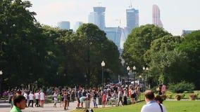 La gente ed i bambini si rilassano sull'attrazione nella città in parco sulle vie di Mosca stock footage