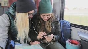 La gente elegante del teléfono que comparte y que mira la risa video divertida mientras que viaja en tren encendido conmuta metrajes