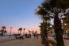 La gente en la acera en Finikoudes vara, tomando un paseo en la puesta del sol Fotografía de archivo libre de regalías