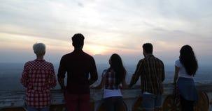 La gente en de la montaña del top vista posterior detrás que disfruta del paisaje, amigos agrupa a los turistas que miran salida  almacen de metraje de vídeo