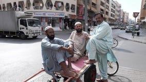 La gente en el área de Dubai viejo en ropa nacional asiática se está colocando cerca de los cruces al lado del carrito para almacen de video