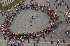 La gente en el cuadrado recolectó en un círculo alrededor del músico a Imagen de archivo