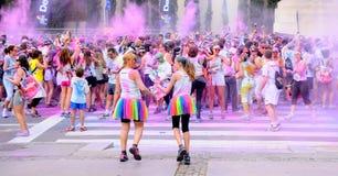 La gente en el funcionamiento del color de Holi va de fiesta en las calles de la ciudad fotos de archivo