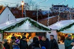 La gente en el mercado de la Navidad con las decoraciones en la catedral ajusta Vilna Foto de archivo