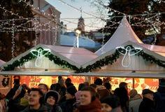 La gente en el mercado de la Navidad con las decoraciones en catedral ajusta Vilna Fotos de archivo