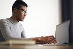 La gente en el trabajo que enviaba obsevaciones sobre la caja del correo electrónico vía el ordenador portátil conectó con el wif Imágenes de archivo libres de regalías