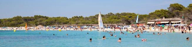 La gente en Es Trenc vara con el mar blanco de la arena y de la turquesa Imagen de archivo