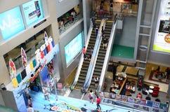 La gente en la escalera móvil es una escalera móvil en la alameda de compras Imagen de archivo libre de regalías