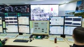 La gente en los monitores comprueba proceso en la planta de refinería del gas almacen de video