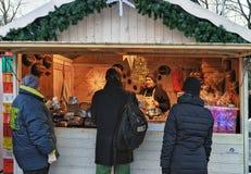 La gente en la Navidad atasca en mercado de Navidad en el cuadrado de la catedral Imagen de archivo libre de regalías