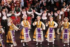 La gente en trajes tradicionales del folclore realiza la danza popular Horo b?lgaro imagen de archivo