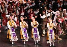La gente en trajes tradicionales del folclore realiza la danza popular Horo b?lgaro fotos de archivo