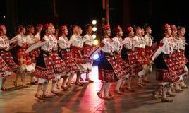 La gente en trajes tradicionales del folclore realiza horo búlgaro de la danza popular en feria nacional del folclore en la Sofía imagenes de archivo