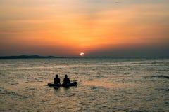 La gente en una balsa está mirando una puesta del sol colorida en Zadar, Croacia foto de archivo