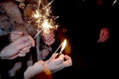 La gente encendió las bengalas debajo del reloj chiming por el Año Nuevo fotos de archivo