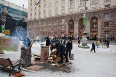 La gente enciende el fuego en barriles en la calle escarchada del invierno delante de la administración de la ciudad durante prote Fotos de archivo