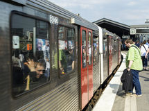 La gente entra en el tren en la estación de Baumwall en Hamburgo Foto de archivo