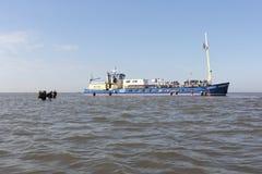 La gente esce della barca e della passeggiata attraverso l'acqua verso l'isola Griend del Wadden Fotografia Stock
