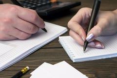 La gente escribe en las manijas del cuaderno, teléfono Imagen de archivo