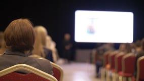 La gente escucha la presentación la sala de conferencias Visión posterior Hombres de negocios del seminario de la conferencia del