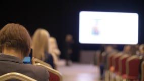 La gente escucha la presentación la sala de conferencias Visión posterior Hombres de negocios vacíos del seminario de las sillas