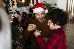 La gente está adornando el árbol de navidad Imágenes de archivo libres de regalías