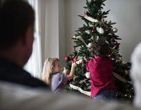 La gente está adornando el árbol de navidad Imagen de archivo libre de regalías