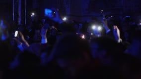 La gente está bailando sosteniendo los teléfonos móviles encendidos por la tarde en un cierto concierto almacen de video