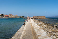 La gente está caminando a lo largo de la pared del puerto en la ciudad de Chania en la isla de Creta Fotografía de archivo libre de regalías