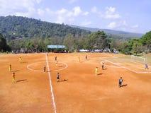 La gente está jugando a fútbol en la tierra Fotografía de archivo libre de regalías
