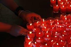 La gente está quemando la quema roja de las velas Foto de archivo libre de regalías