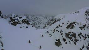 La gente está subiendo en la colina de una montaña durante la ventisca, cantidad aérea en 4k almacen de metraje de vídeo