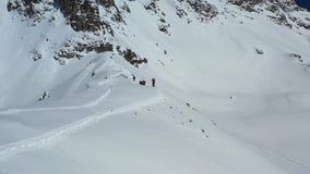 La gente está subiendo las colinas de una montaña cubierta en la nieve, cantidad aérea en 4k metrajes