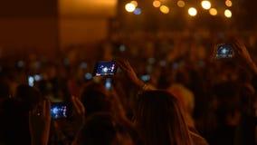 La gente está tomando las imágenes del concierto musical con los teléfonos, colocándose en sitio oscuro metrajes