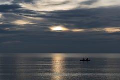 La gente está tomando un bote pequeño del kajak mientras que el sol está fijando Imagenes de archivo