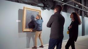 La gente está viendo la imagen en la galería, trabajador está llevando de ella de pasillo almacen de metraje de vídeo
