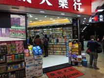 La gente fa gli acquisti in una farmacia locale in Hong Kong fotografie stock libere da diritti