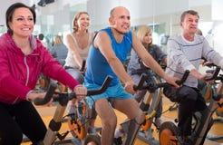 La gente fa gli sport sulle bici di esercizio Immagine Stock Libera da Diritti