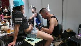 La gente fa i tatuaggi alla decima convenzione internazionale del tatuaggio nel centro dell'Congresso-EXPO video d archivio