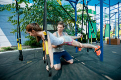 la gente fa l'addestramento della sospensione con le cinghie di forma fisica all'aperto Immagini Stock