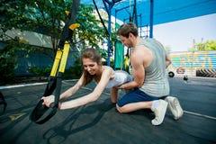 la gente fa l'addestramento della sospensione con le cinghie di forma fisica all'aperto Fotografie Stock
