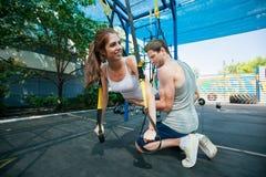 la gente fa l'addestramento della sospensione con le cinghie di forma fisica all'aperto Immagine Stock