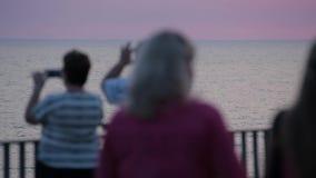 La gente fa le foto Tramonto al mare Nel defocus archivi video