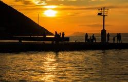 La gente, familias está mirando la puesta del sol en Croacia, Trpanj Foto de archivo