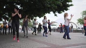 La gente felice che balla sulla via, manifestazioni del coreografo balla i movimenti per la femmina allegra all'aperto, stock footage