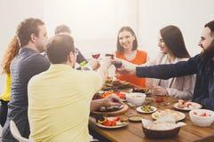 La gente feliz dice los vidrios del tintineo de las alegrías en el partido de cena festivo de la tabla Fotografía de archivo
