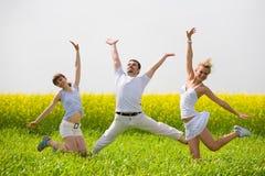 La gente feliz está saltando en campo Fotos de archivo libres de regalías