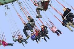 La gente feliz juega el chairoplane en un parque de atracciones Fotos de archivo libres de regalías